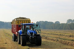 Tractor and silage wagon with grass on field Royalty Free Stock Photos