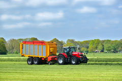 Tractor and silage wagon. Tractor and a Self-loading and harvester-filled forage wagon collecting mowed grass. Logo and trademarks removed Stock Image