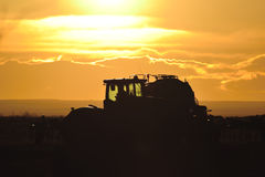 Farm Tractor Silhouette. A Farm tractor waits in a field at dusk, with its seeding  equipment back-lighted by a bright orange sunset Stock Photos