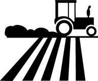 Tractor. Silhouette of a tractor running on the field which causes dust Royalty Free Stock Photography