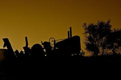 Tractor Silhouetted in Sunset. An old tractor hooked to a pull type combine with an auger is silhouetted in the sunset.  combine Stock Photos