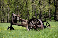 Tractor skeleton parked in a field with dandelions Stock Photo
