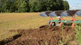 Tractor slowly ploughing farm field soil