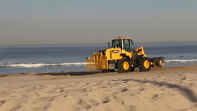 Tractor smoothing beach stock footage