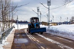 Tractor on the snow-covered street. stock photos