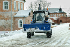 Tractor with snowplowing equipment cleans road Stock Photos