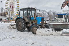 Tractor with snowplowing equipment cleans street Royalty Free Stock Photos