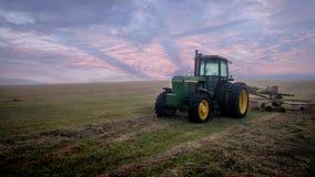 Tractor solitario por la mañana en un campo grande Foto de archivo libre de regalías