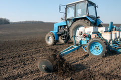 Tractor with sower on the field Stock Photography