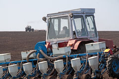 Tractor with sower on the field Royalty Free Stock Photo