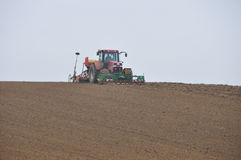 Tractor sowing. Farm tractor sowing a field at horizon Royalty Free Stock Photography