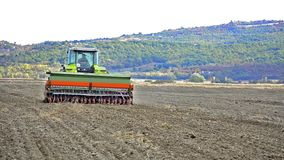 Tractor sowing and cultivating field Stock Photos
