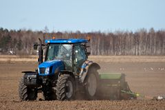 Tractor sowing seed. In sprig royalty free stock photo