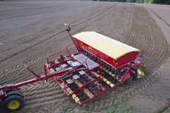 Tractor sowing seeds in freshly plowed field Royalty Free Stock Photos