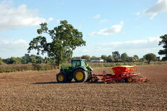 A tractor sows seed in a field. Stock Photo
