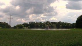 Tractor spray crop field with sprayer pesticide. Village work stock video footage