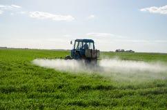 Tractor spray fertilize field pesticide chemical. Tractor spray fertilize green field with pesticide insecticide herbicide chemicals in agriculture field in stock images
