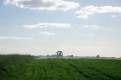 Tractor spray field with chemicals and worker man Royalty Free Stock Photography