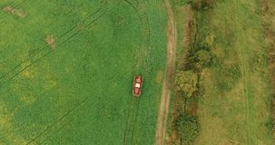 Tractor Spray Green Crop Field Near Village Houses in Autumn stock footage
