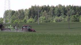Tractor spray green summer corn field pesticide near wiring pole Royalty Free Stock Photos