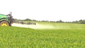 Tractor spray liquid fertilizer on crop field. Agrucultural work stock footage