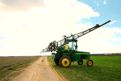 Tractor sprayer on open field. A tractor sprayer next to an old dirt path royalty free stock image