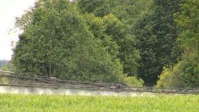 Tractor sprayer sitting stream with fertilizer on crop field stock video