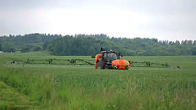 Tractor and Sprayer on Wheat Field Stock Images