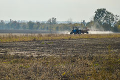 Tractor spraying autumn field. On a sunny day Royalty Free Stock Photo