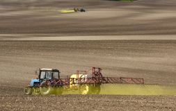 Tractor spraying the chemicals on the field. tractor sprinkling royalty free stock photo