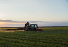 Tractor spraying crops at sunset Stock Photos