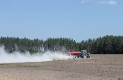 The tractor is spraying fertilizer in a field Stock Photo