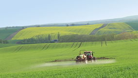 Tractor Spraying Fertilizer on Spring Field. Czech Republic. Spring fields of southern Moravia. Small tractor rides through the hills and spraying fertilizer on stock video