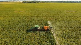 Tractor is spraying fertilizers field. Aerial view tractor spraying the chemicals on the large green field. Spraying the herbicides on the farm land. Treatment Royalty Free Stock Photography