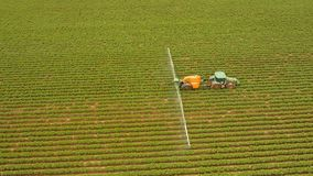 Tractor is spraying fertilizers field. Aerial view tractor spraying the chemicals on the large green field. Spraying the herbicides on the farm land. Treatment Royalty Free Stock Images