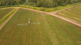 Tractor is spraying fertilizers field. Aerial view tractor spraying the chemicals on the large green field. Spraying the herbicides on the farm land. Treatment Royalty Free Stock Image