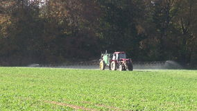 Tractor  spraying  fertilizers pesticides on rapeseed field stock video