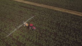 Tractor is spraying fertilizers potato field.Aerial video. stock video footage