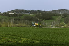 Tractor spraying field Stock Photography