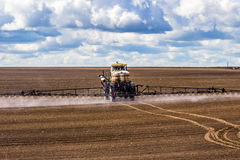Tractor spraying a field on farm, fertilizes the land. Royalty Free Stock Photography