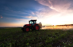 Tractor spraying a field on farm in spring. Royalty Free Stock Image