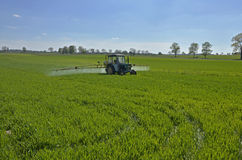 A tractor spraying the field stock photos