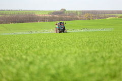 Tractor spraying a green field on a farm Royalty Free Stock Photography
