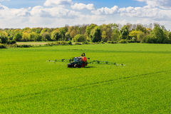 Tractor spraying glyphosate pesticides on a field Stock Images