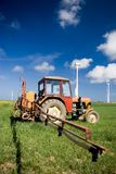 Tractor spraying green field. A small tractor spraying over a green field, wind turbines in the background, intensive blue sky with some white clouds Stock Photography
