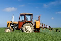 Tractor spraying green field. A small tractor spraying over a green field,  intensive blue sky with some white clouds Royalty Free Stock Photography