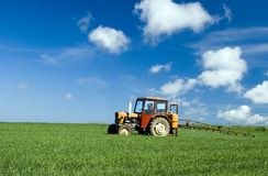 Tractor spraying green field Royalty Free Stock Photo
