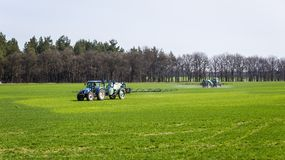 Tractor spraying insecticide to the green field, agricultural na. Tural seasonal spring background Royalty Free Stock Image