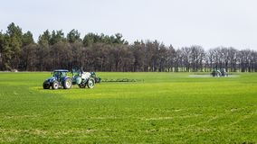 Tractor spraying insecticide to the green field, agricultural na. Tural seasonal spring background Stock Photos