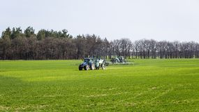 Tractor spraying insecticide to the green field, agricultural na. Tural seasonal spring background Stock Image